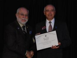 "Prof. Erdal Ozkan, receiving the ""Fellow"" plaque from ASABE President Maynard Herron."