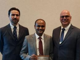 Ajay Shah (center) receiving his award